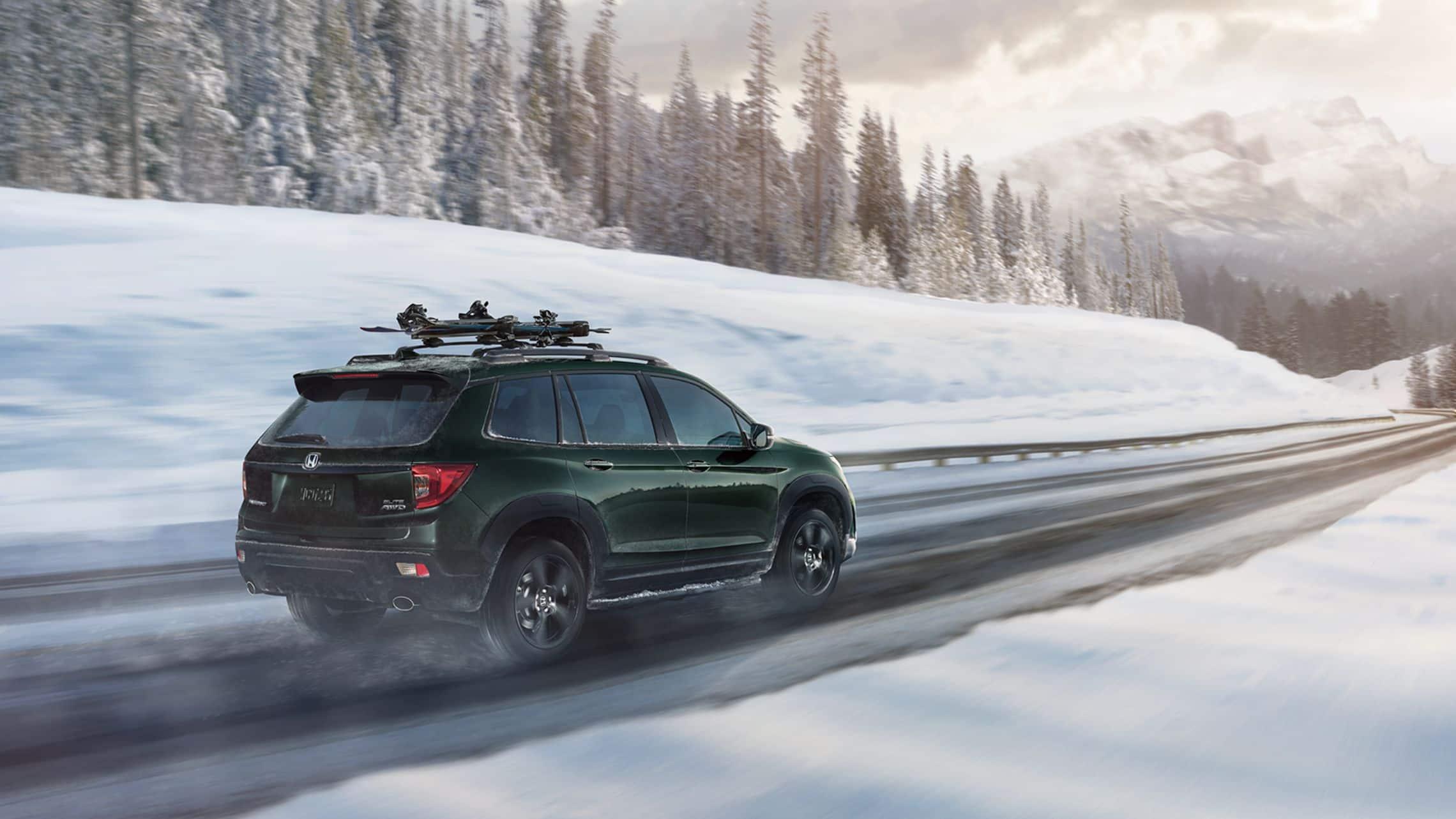 Vista de 3/4 desde la parte trasera del lado del pasajero de la Honda Passport Elite2019 con tracción integral en Black Forest Pearl con accesorio portaesquís/portatablas de snowboard conduciendo por un camino de montaña nevado.