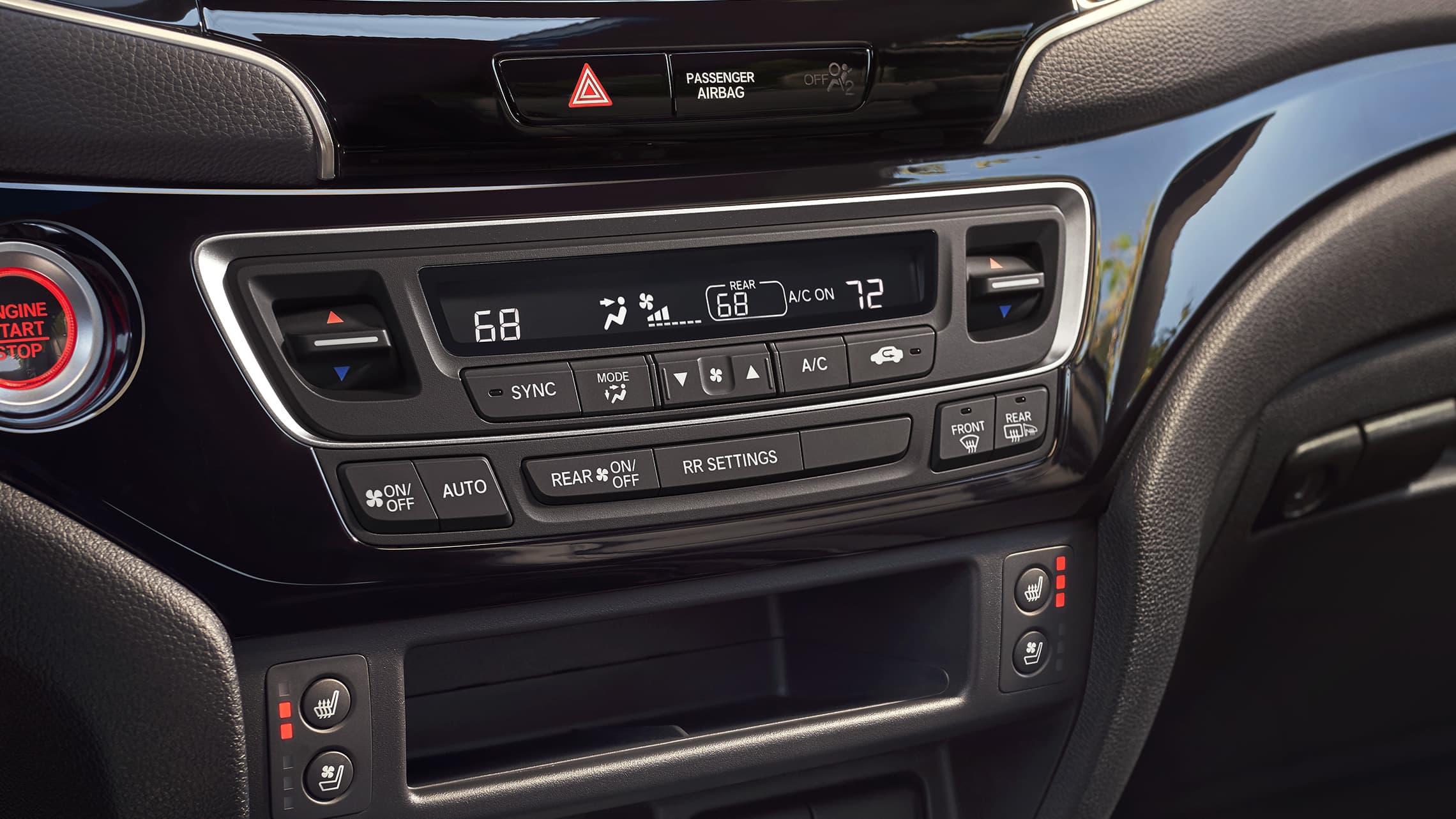 Detalle del control de clima de tres zonas en la Honda Passport Elite2019 con interior en Black Leather.