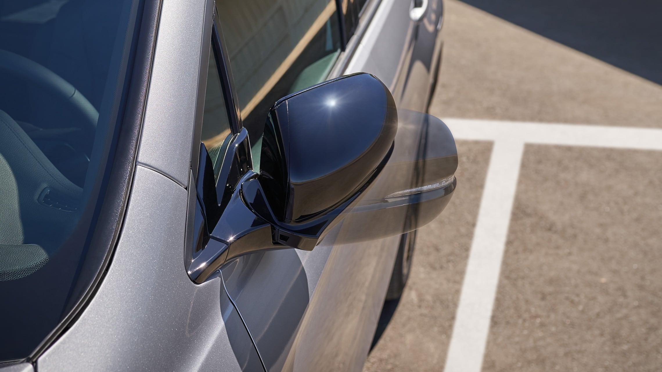 Honda Passport Elite2019 en Lunar Silver Metallic demostrando el movimiento del espejo lateral con pliegue eléctrico y atenuación automática.