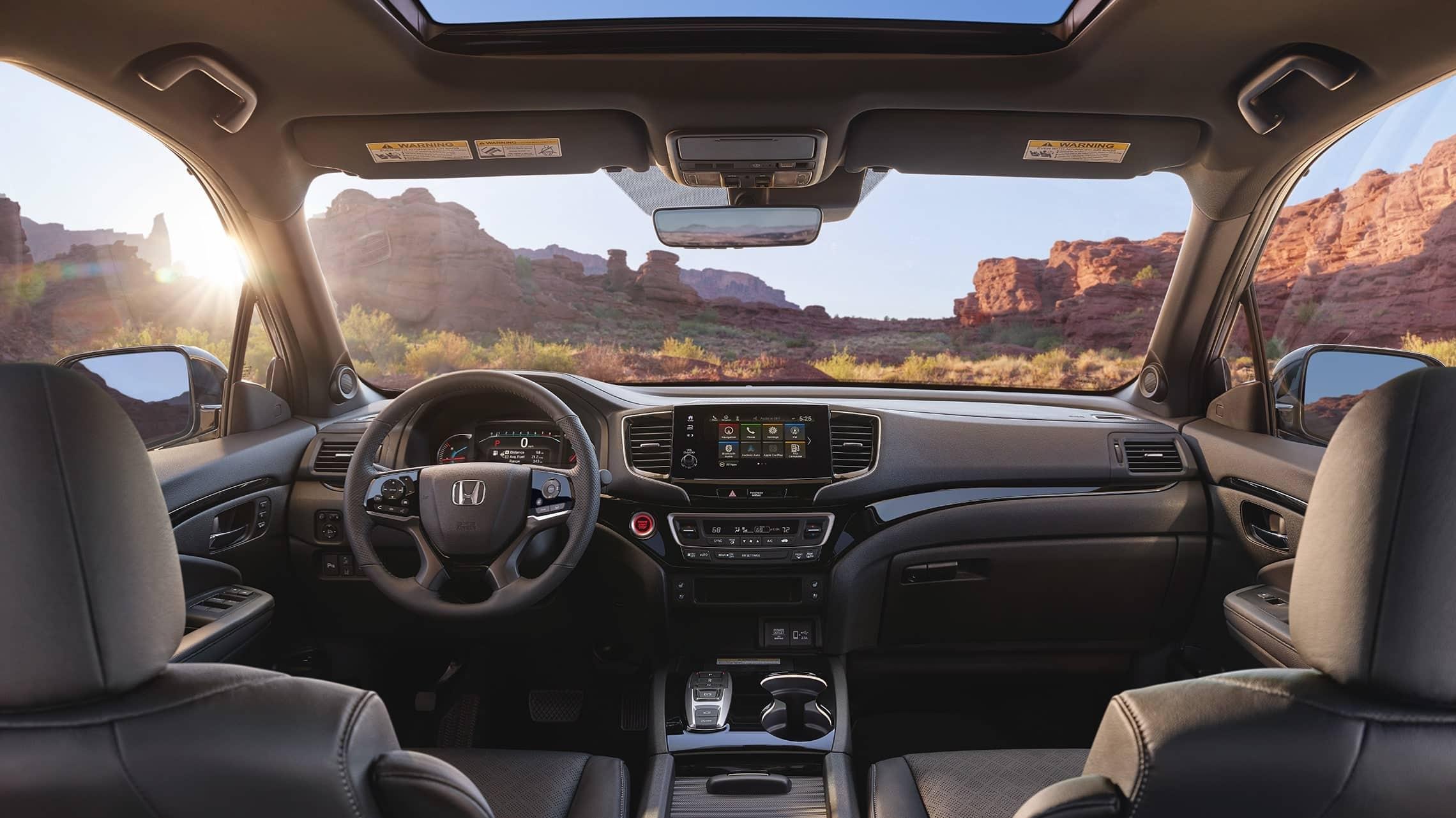 Vista del interior de la Honda Passport Elite2019 en Black Leather que muestra el panel de instrumentos principal, con la integración con Apple CarPlay™ en la pantalla táctil del sistema de audio.