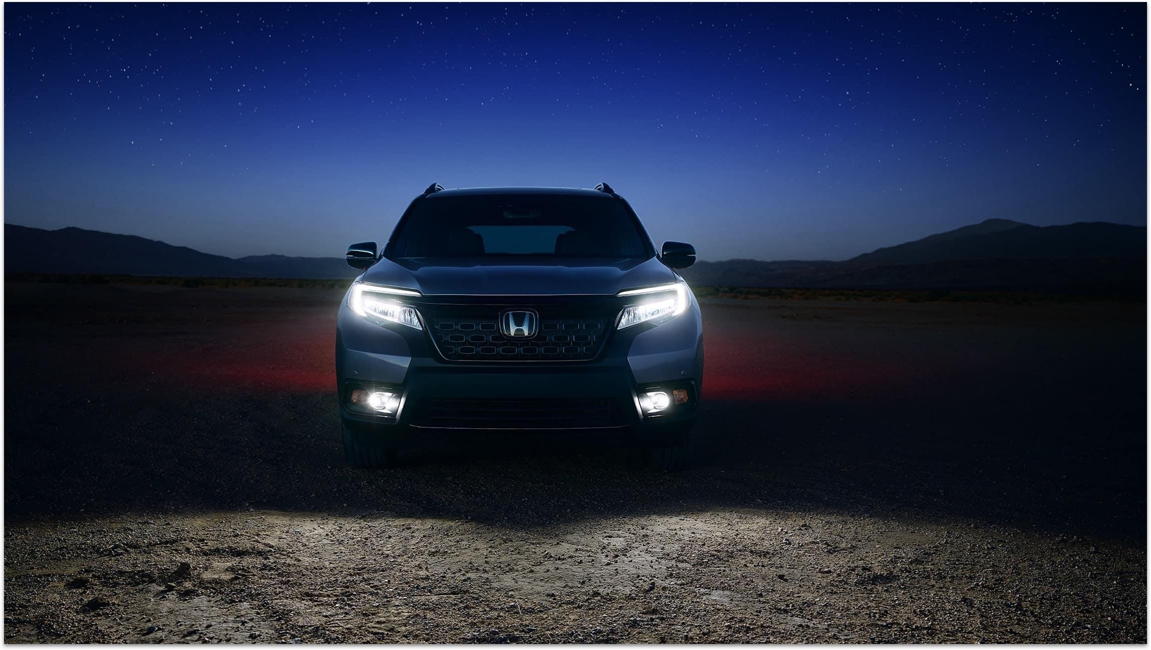 Vista frontal directa de la Honda Passport Elite2019 en Modern Steel Metallic con luces delanteras bajas de LED y faros antiniebla encendidos.