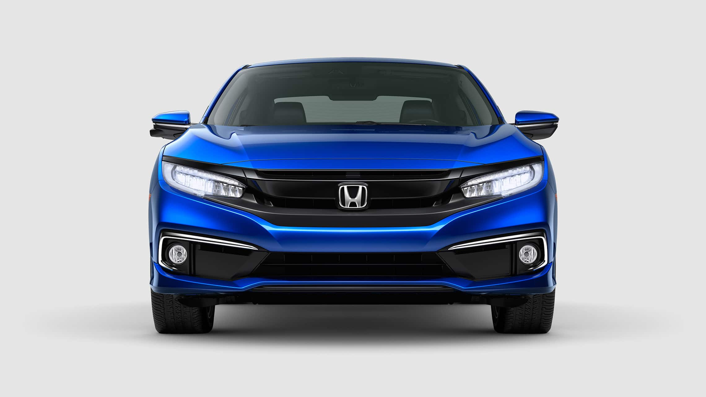 Front view of the 2020 Honda Civic Touring Coupe in Aegean Blue Metallic with LED headlights on.