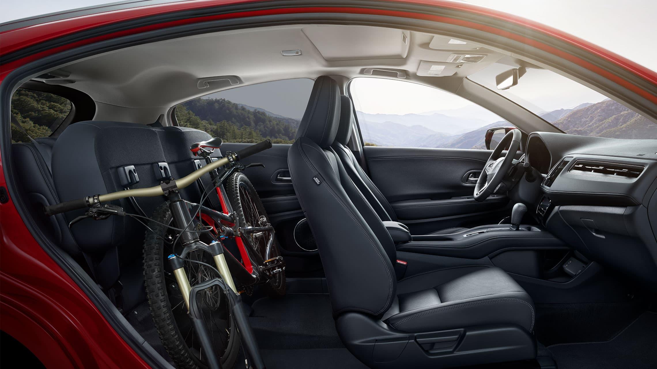 Vista interior desde el lado del pasajero de la Honda HR-V Touring2020 con Black Leather con los asientos traseros abatidos llevando una bicicleta.