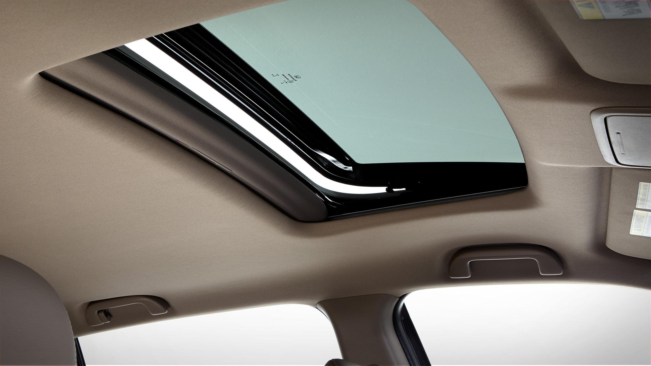 Detalle de la activación del techo corredizo con un toque en la Honda Ridgeline ETL-E 2020 con cuero Beige.