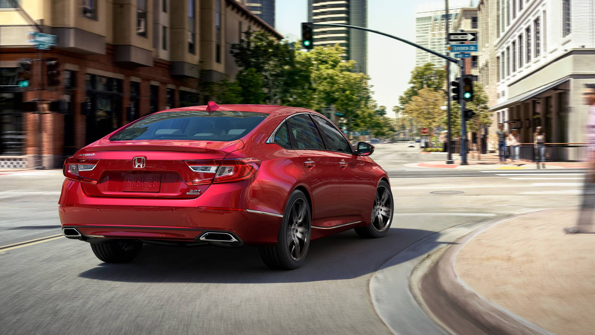 2021 Honda Accord Touring 2.0T in Radiant Red Metallic, making a turn at a downtown intersection.