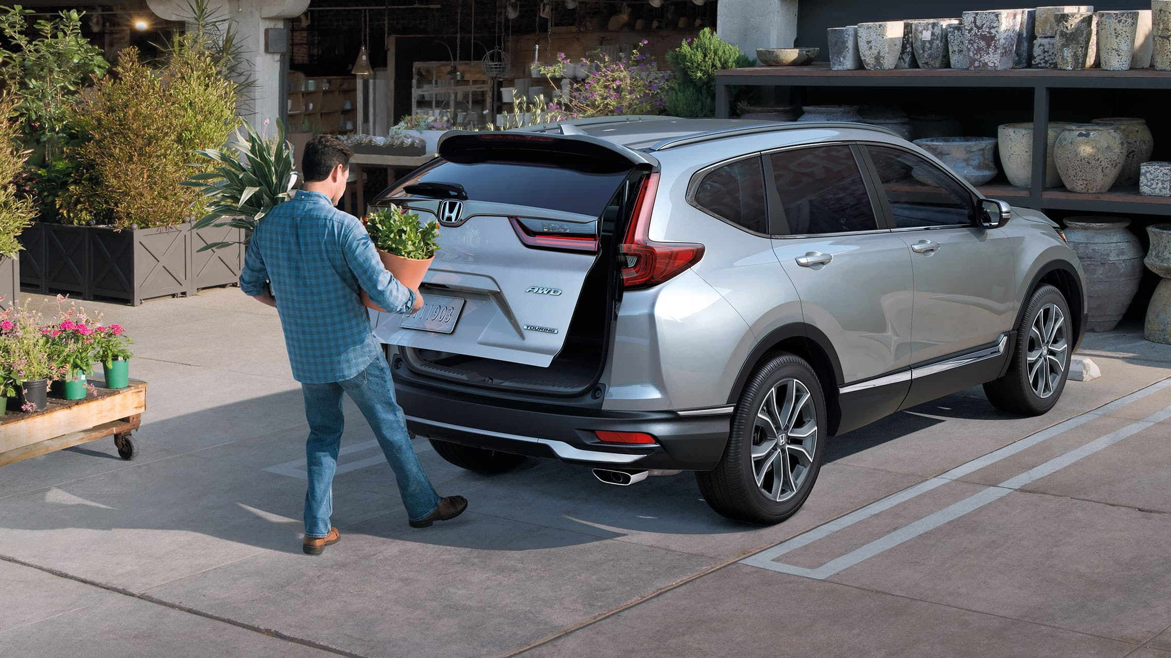 Rear passenger-side view of the 2021 Honda CR-V Touring in Lunar Silver Metallic demonstrating hands-free access power tailgate.