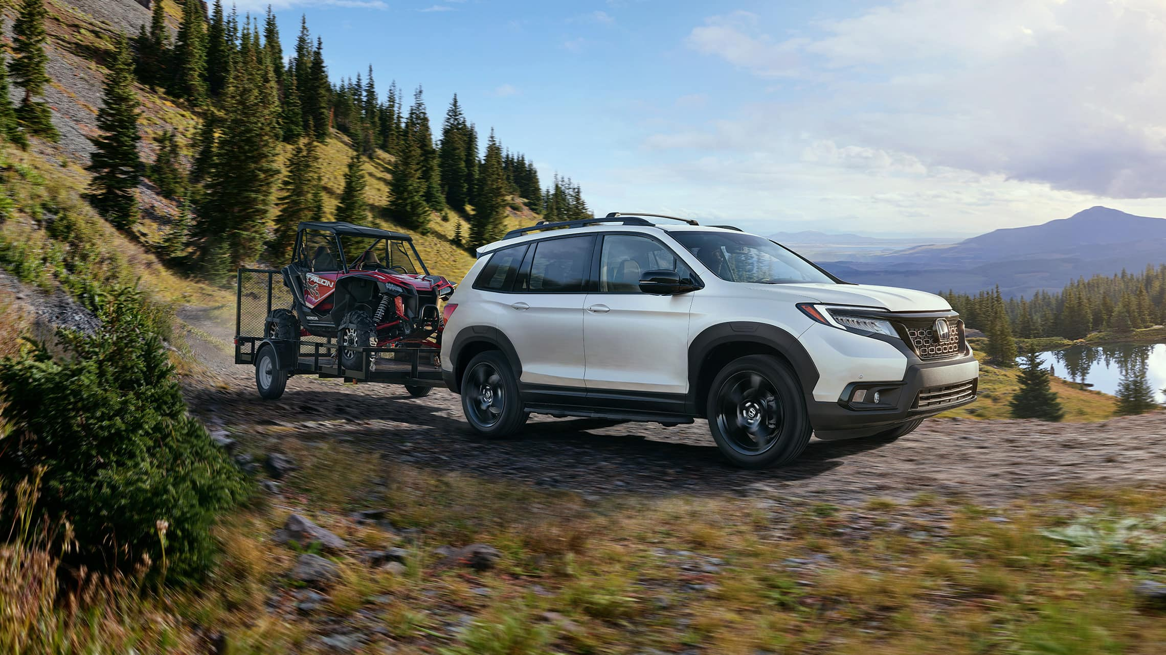 Passenger-side front view of the 2021 Honda Passport Elite in White Diamond Pearl with accessory tow hitch.