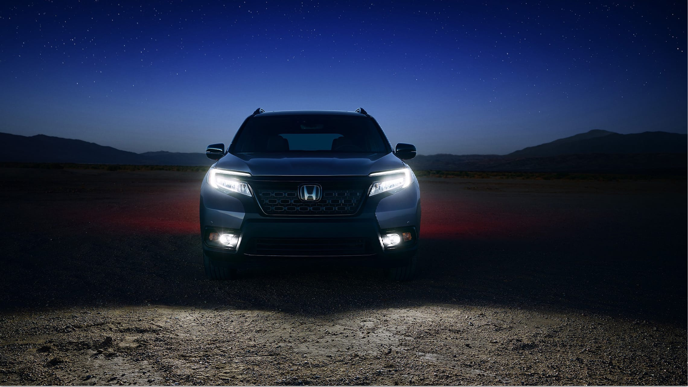Direct front view of the 2021 Honda Passport Elite in Modern Steel Metallic with LED low-beam headlights and fog lights on.
