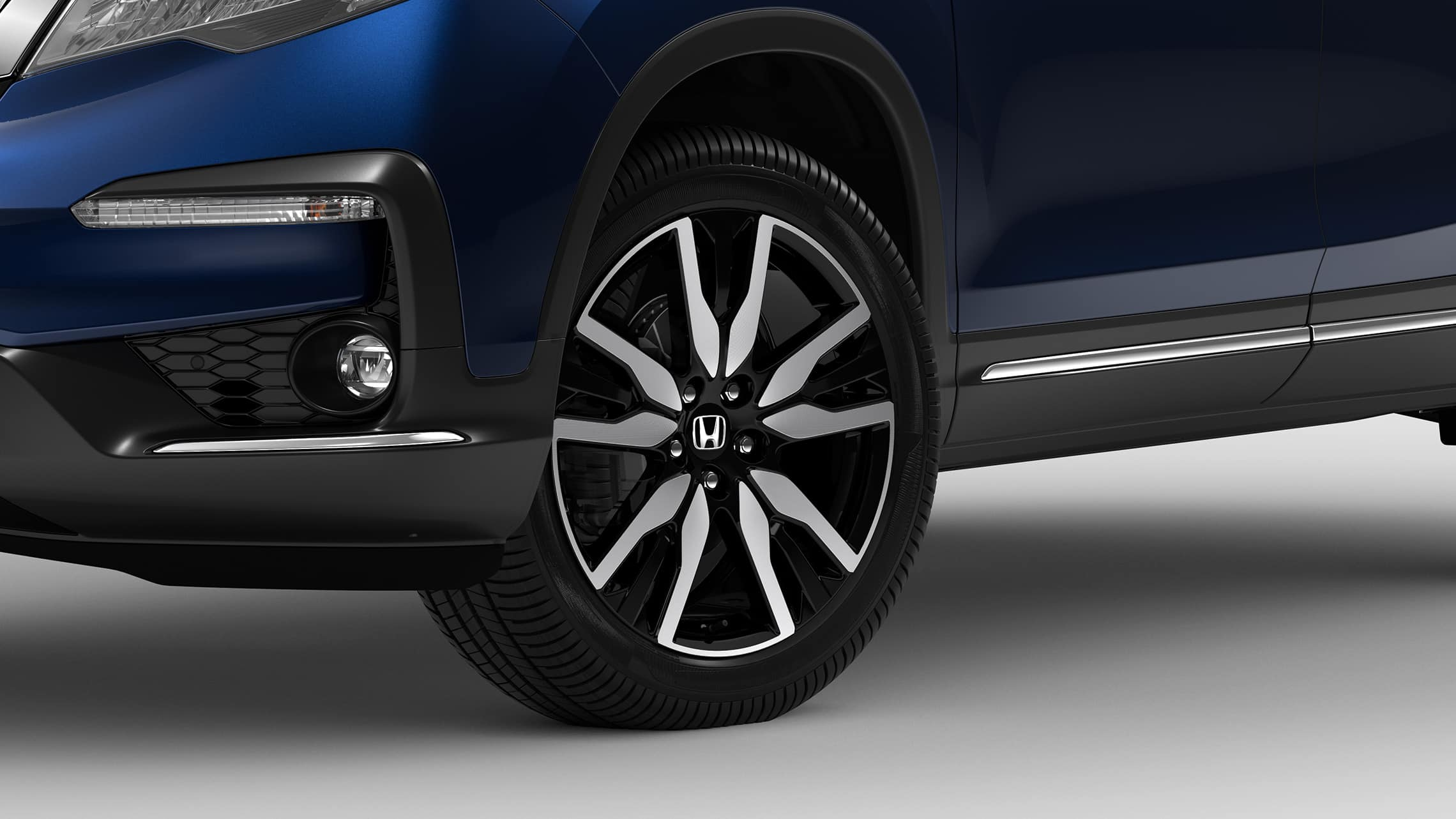 Vista frontal en primer plano de 3/4 desde el lado del conductor de la rueda de aleación de 20pulgadas y detalle del neumático en la HondaPilotElite2021 en Obsidian Blue Pearl.